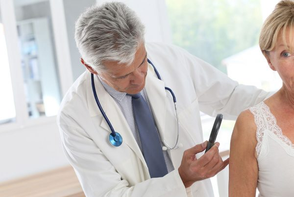 Dermatologist looking at patients skin